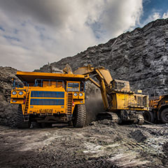 Image shows mining truck and excavator in front view